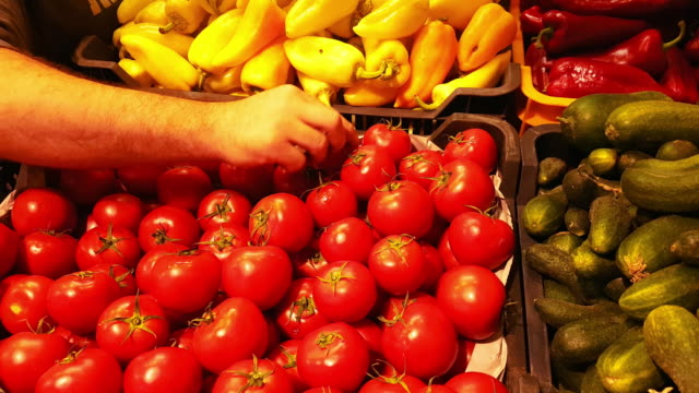 Market Vendor Arranging Fresh Tomatoes On Display