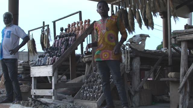 market vendors seeling voodoo fetishes at he akodessawa fetish market or marche des feticheurs in lome, togo - fetischismus stock-videos und b-roll-filmmaterial