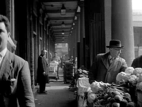 Market worker walks along colonnade at Covent Garden Market 1950's