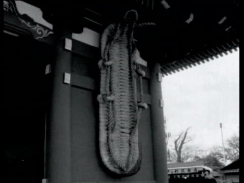 vídeos de stock, filmes e b-roll de marketplace in old tokyo / buddhist temple asakusa / large slipper on wall / visitors rubbing healing smoke over themselves / man ladling purifying... - 1964