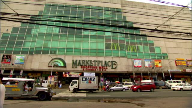 marketplace shopping mall building w/ unidentifiable people walking traffic on general kalentong street fg jeepney street vendor city metro manila - luzon stock videos & royalty-free footage