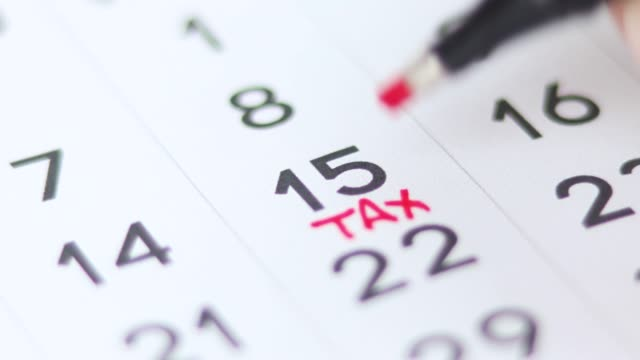 marking the number 15 and tax day on the calendar. 4k video. - tax form stock videos & royalty-free footage