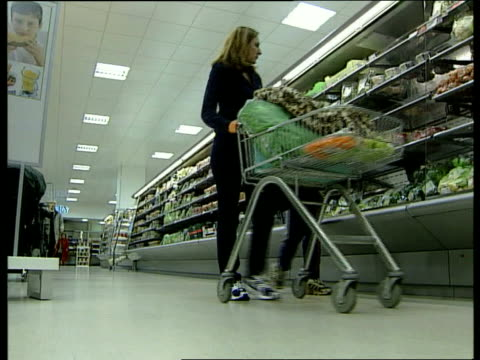 Marks and Spencer profits continue to fall LIB MS Woman along thru food department with trolley BV Women looking at food