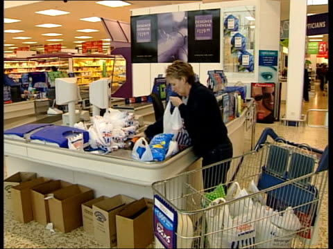 vídeos de stock, filmes e b-roll de marks spencer christmas sales down tesco goods passed thru checkout at tesco supermarket ms woman along in supermarket with chairs on trolley pan... - woolworths