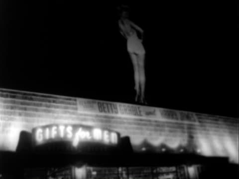 Marquee advertising performance by Harry James Betty Grable at Opera House in Las Vegas Nevada / PAN well dressed white men women standing outside /...