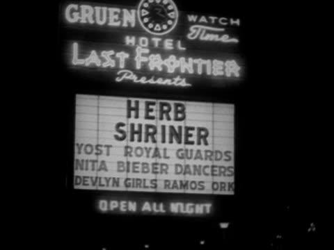 marquee w/ 'hotel last frontier' in neon at top, featuring herb shriner as headliner w/ yost royal guards, nita bieber dancers, devlyn girls, ramos... - 1952 bildbanksvideor och videomaterial från bakom kulisserna