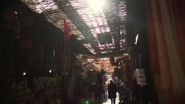 Marrakech souks at daytime. People passing through.