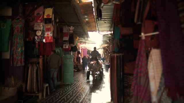 Marrakech Souks at daytime. Three carriages pass by.