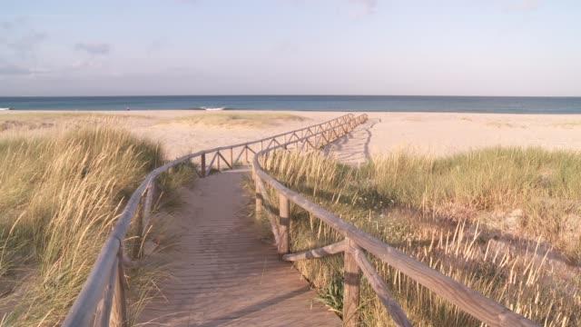 Marram grass surrounds a walkway near a beach in Tarifa, Spain.