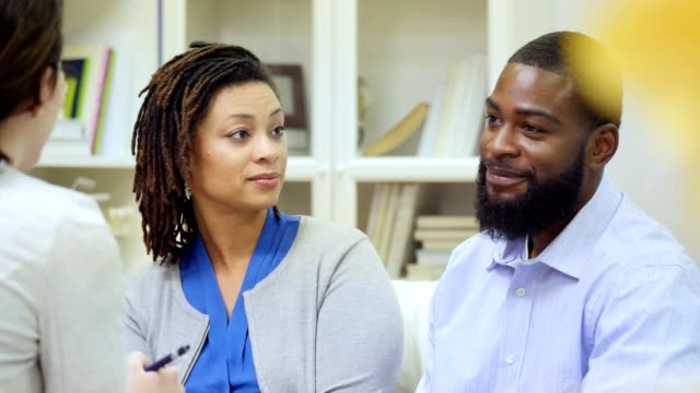 Married African American couple discuss issues with counselor