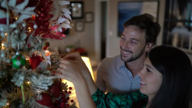 vídeos de stock, filmes e b-roll de pares casados que decoram a árvore de natal em casa - árvore de natal