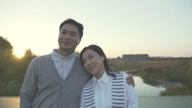 vídeos de stock e filmes b-roll de a married couple enjoying beautiful scenic in the park - cara para baixo