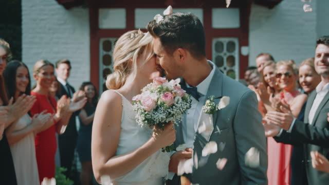 vídeos de stock, filmes e b-roll de pares casados que saem da igreja ao beijar ao ar livre - casamento