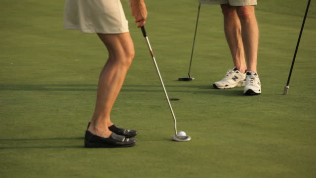 ms, married couple playing golf on putting green, eastville, virginia, usa - putting green stock videos & royalty-free footage