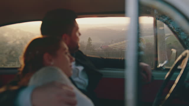 married couple sitting inside car and admiring view during sunset - stationary stock videos & royalty-free footage