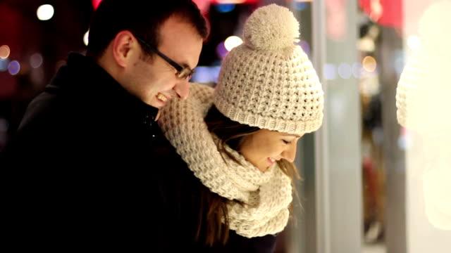 vídeos de stock e filmes b-roll de casado casal equilibrar em um show-janela da loja - fachada
