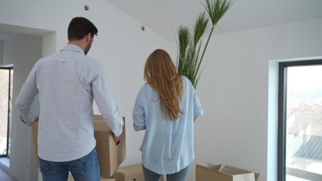 married couple unpacking the box in their new house and planning the interior arrangement - young couple stock videos & royalty-free footage