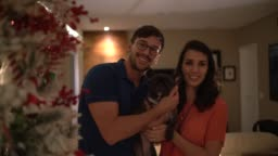 Married Couple with Dog Celebrating Christmas Time at Home - Portrait