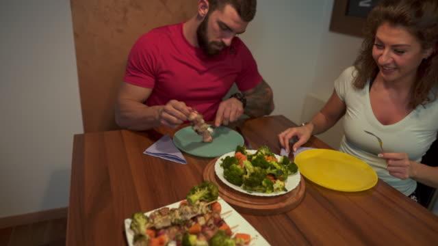 stockvideo's en b-roll-footage met getrouwd fitness koppel eten - piercen