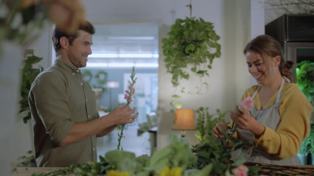 married flower shop owners flirt while they remove leaves from rose stems - straight hair stock videos & royalty-free footage