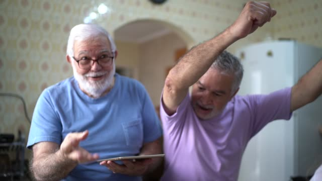 married gay couple / senior friends cooking and dancing - senior adult stock videos & royalty-free footage