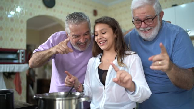 vidéos et rushes de couple gay marié / senior amis cuisiner avec les fille - famille multi générations