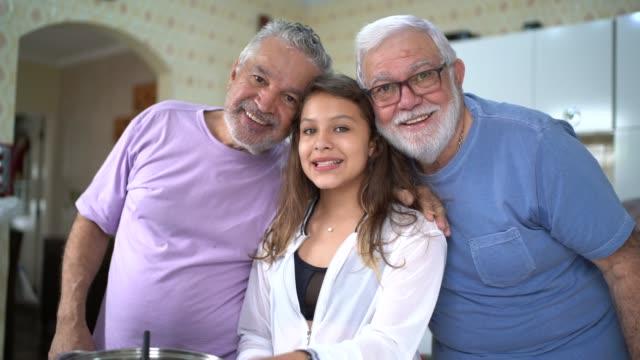 vídeos y material grabado en eventos de stock de matrimonio gay / senior amigos cocinando con hija - pareja mayor