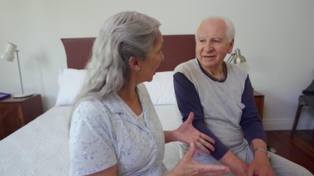 stockvideo's en b-roll-footage met getrouwd senior paar praten op bed in de ochtend - woongemeenschap ouderen