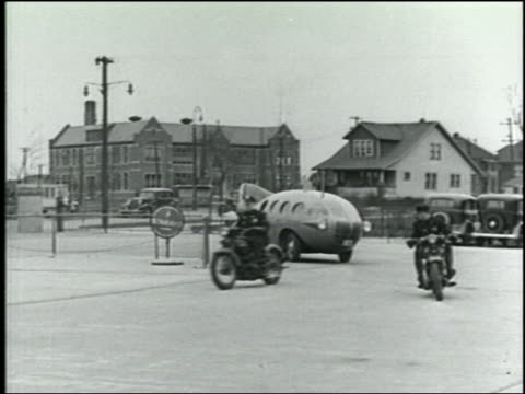 "vídeos de stock, filmes e b-roll de b/w 1934 pan ""mars express"" rocket car following 2 policemen on motorcycles around corner - carro foguete"