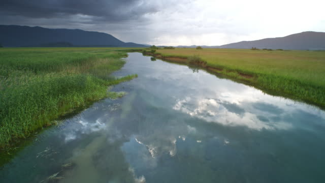 AERIAL Marsh river reflecting grey stormy clouds on its peaceful surface
