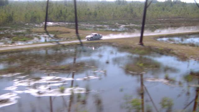 a u.s. marshal drives fast through a swamp. - 湿地点の映像素材/bロール