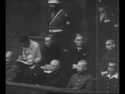 Marshal of the court reads from document during session of Tokyo war crimes tribunal / defendants in dock / tiltdown shot Japanese political...