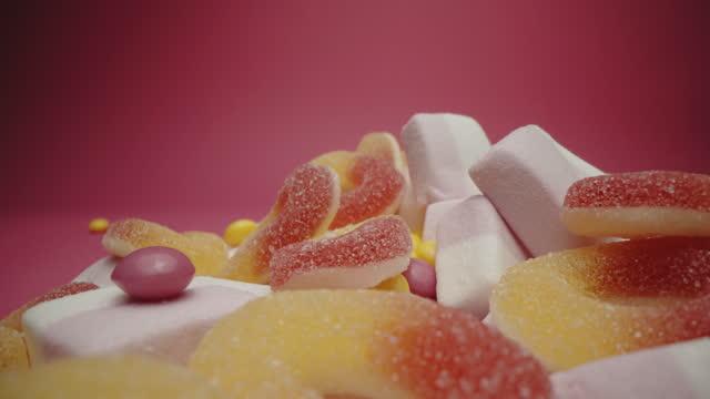ピンクの背景にマシュマロ、ゼリービーンズとカラフルな酸っぱいキャンディー - ジェリービーンズ点の映像素材/bロール