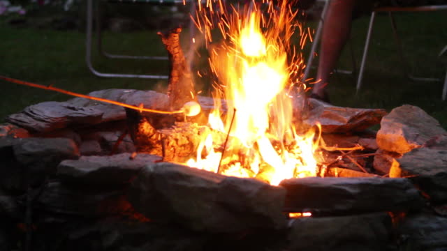 Marshmallows are roasted over a backyard fire.