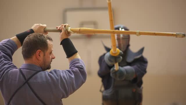 vidéos et rushes de professeur d'art martial, ayant un duel avec un étudiant, au cours de leur formation de kendo - s'entraîner