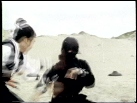martial arts fight sequence outdoors / men dressed in black with masks jump out of the ground and fight with a man and a woman martial arts fight... - カンフー点の映像素材/bロール