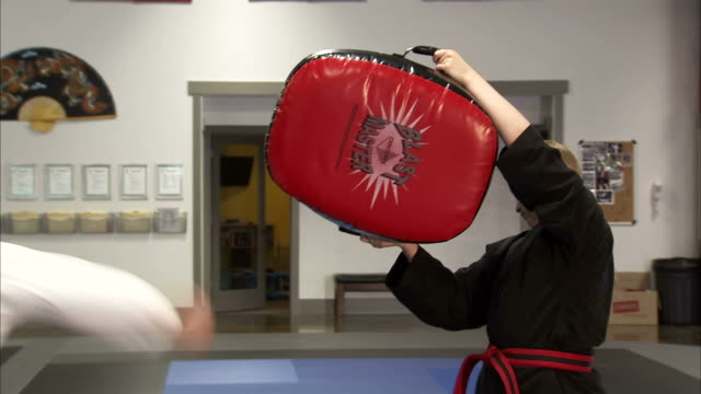 ms pan martial arts instructor kicking bag held up by woman / springville, utah, usa - springville utah stock-videos und b-roll-filmmaterial