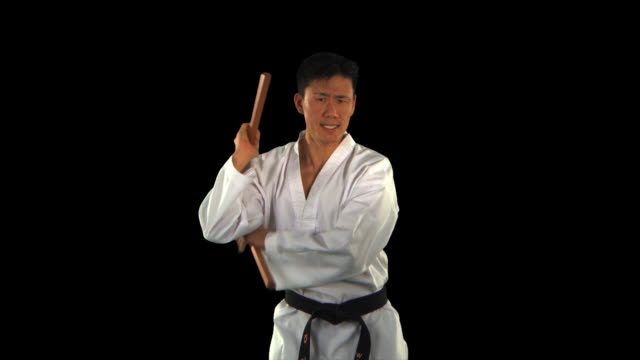 stockvideo's en b-roll-footage met martial arts master swinging nunchucks close-up - this clip has an embedded alpha-channel - keyable