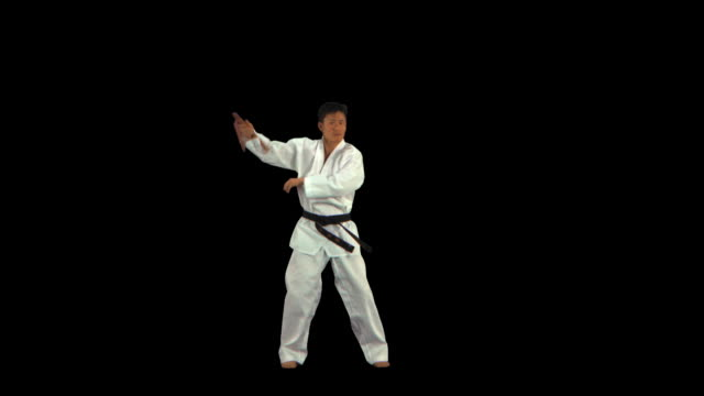 martial arts master swinging nunchucks - this clip has an embedded alpha-channel - pre matted stock-videos und b-roll-filmmaterial