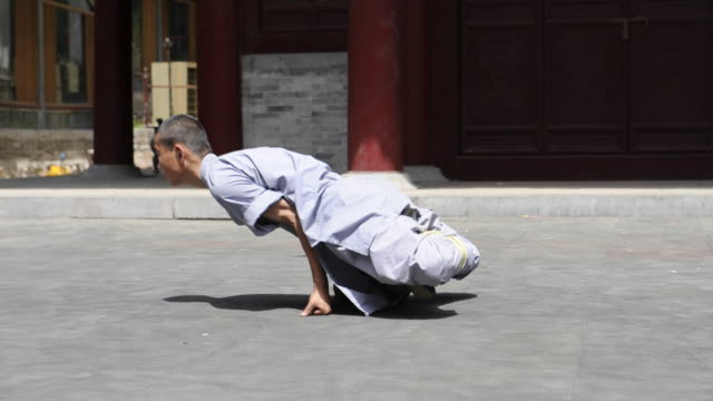 a martial arts student demonstrates flexibility as he sits and contorts his body. - 少林寺点の映像素材/bロール