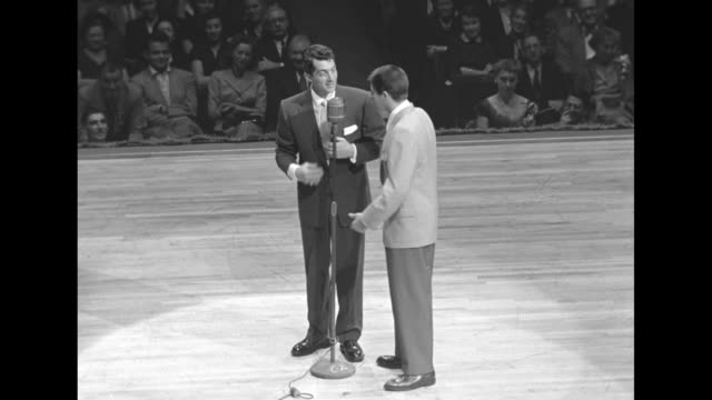martin and lewis on stage, hold hands as lewis jumps around / audience / at microphone they do schtick: martin asks if he wants to sing in unison,... - comedian stock videos & royalty-free footage