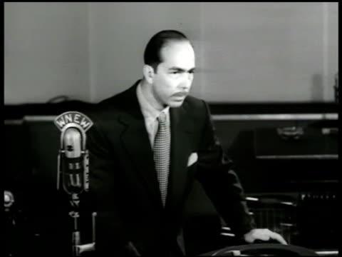stockvideo's en b-roll-footage met martin block standing w/ phonograph listening usa - 1947