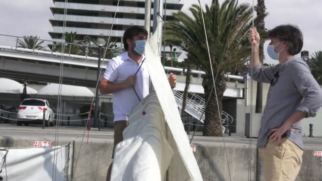 martin cabrera sailing teacher shows how to hoist the mainsail to participant mario while wearing a face mask of escola port 's sailing club at... - participant stock videos & royalty-free footage