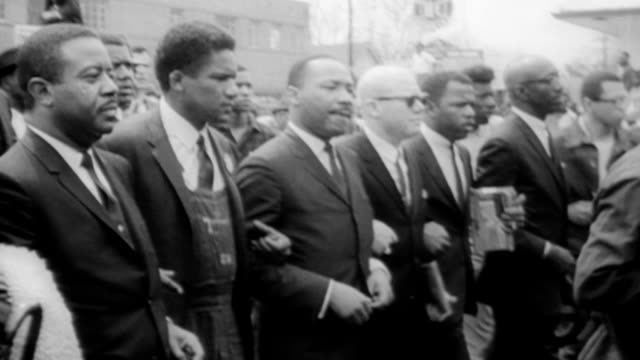vídeos de stock, filmes e b-roll de martin luther king jr marches with his supporters through montgomery to pressure changes in the civil rights voting bill / priests marching arm and... - marchando