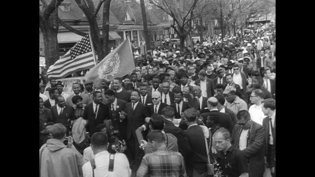 vídeos y material grabado en eventos de stock de cu martin luther king jr walking arms linked with others as he leads a protest march to the racecourse in montgomery alabama/ protestors arrive in... - 1965
