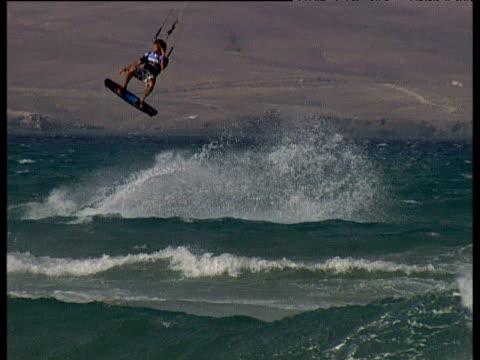 martin vari leaps and twists into air on kite board fuerteventura - eskapismus stock-videos und b-roll-filmmaterial