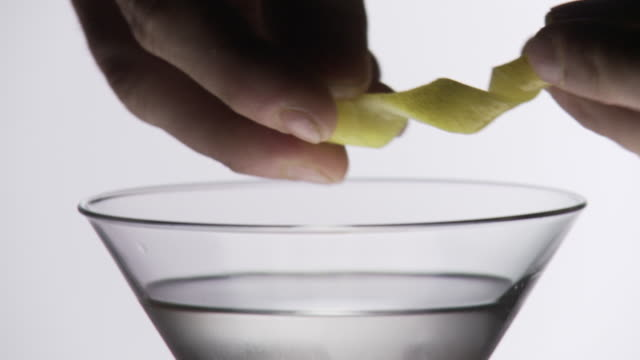 martini cocktail being made, a lemon slice is added in slow motion - twisted stock videos & royalty-free footage