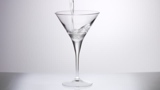 Martini cocktail being poured into glass in slow motion