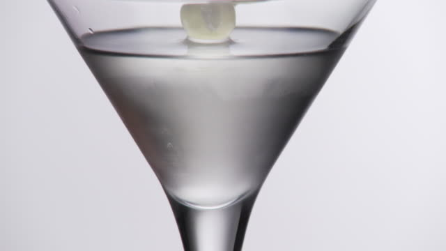 Martini cocktails with olives added slow mo 1