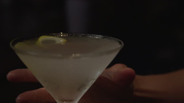 a martini with a lemon twist in a frosted glass is picked up from a table. - martini glass stock videos and b-roll footage
